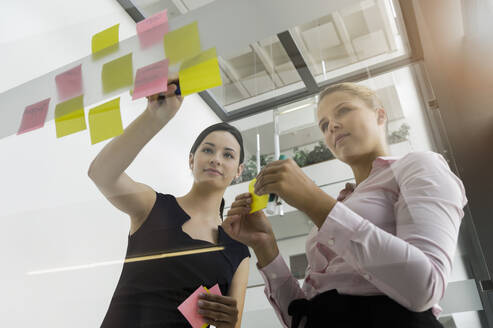 Female professionals sticking adhesive notes on glass wall while discussing in office - BMOF00431