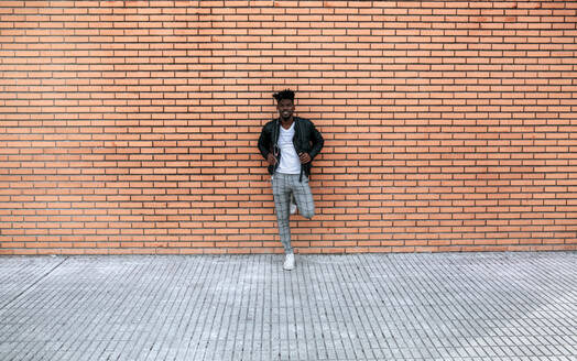 Mid adult man wearing leather jacket standing against brick wall - MGOF04437