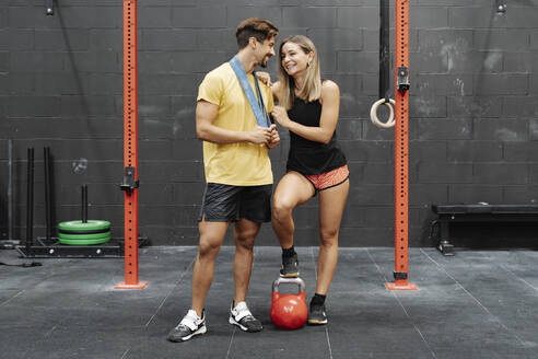 Smiling young couple with kettlebell standing on floor against wall in gym - JCZF00221