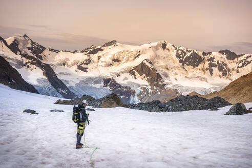 Mature man standing on snowcapped mountain against sky, Stelvio National Park, Italy - MCVF00600