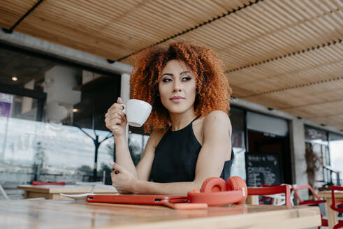 Thoughtful young woman holding coffee cup while sitting at sidewalk cafe - DSIF00119