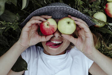 Close-up of cheerful woman holding apples in front of eyes while lying at in orchard - OGF00594