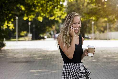 Cheerful young woman holding coffee talking over smart phone while standing in park - BMOF00437