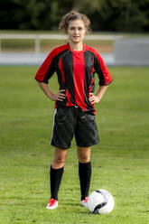 Female player with soccer ball standing on field - STSF02609