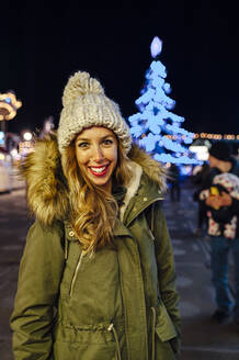 Smiling woman standing in amusement park at night during Christmas - JMPF00404