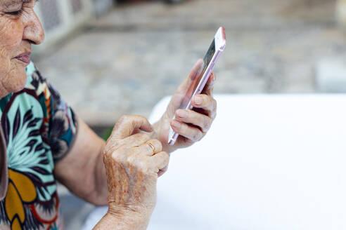 Close-up of senior woman using smart phone at table in yard - PGF00005