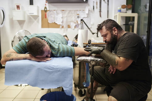 Bearded artist tattooing on male customer's hand lying on bed in studio - SASF00094