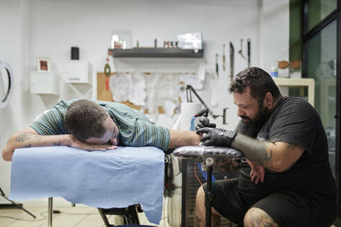 Male artist tattooing on customer's hand in studio - SASF00097