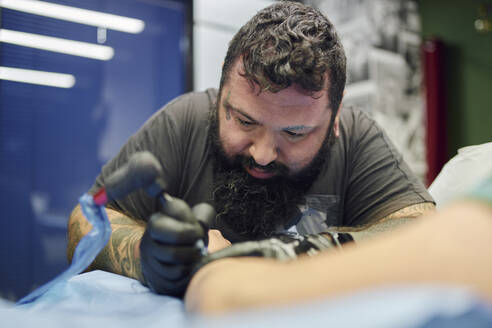 Close-up of bearded artist tattooing on customer's hand in studio - SASF00103
