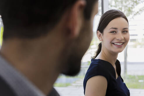 Close-up of smiling businesswoman discussing with male colleague in office - BMOF00445