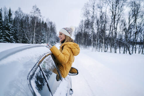 Smiling mature woman sitting on car window against snow covered landscape - DGOF01428