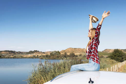 Carefree woman admiring view while sitting on car roof - JSRF01136