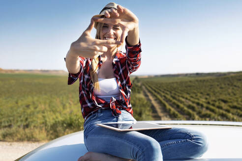 Smiling young woman showing finger frame while sitting on car roof - JSRF01139