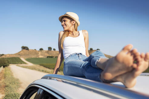 Smiling young woman with legs crossed at ankle sitting on car roof - JSRF01142