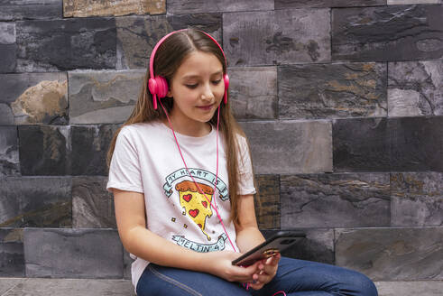 Cute girl with headphones using mobile phone while sitting against wall at home - DSIF00129