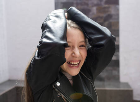 Girl wearing jacket smiling while standing at home - DSIF00132