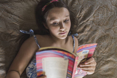 Girl reading book while lying on bed at home - DSIF00138