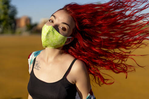 Redhead woman wearing protective face mask while standing outdoors - OCMF01714