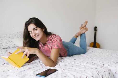 Young woman reading book while lying down on bed at home - XLGF00552