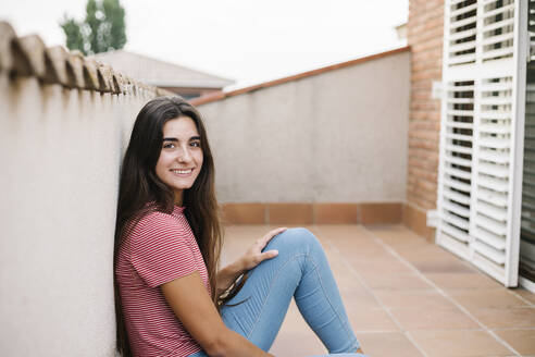 Smiling young woman sitting in balcony - XLGF00561