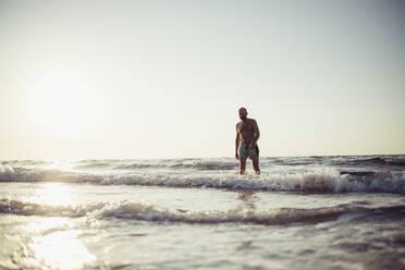 Senior man walking in water at beach - MEUF02072