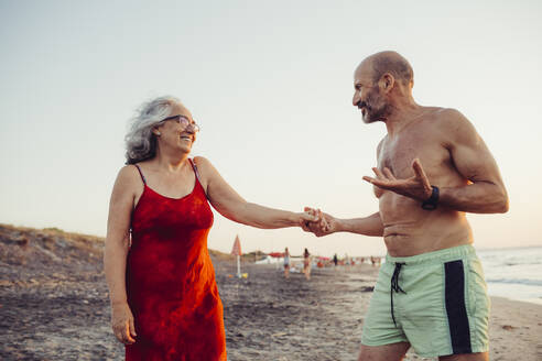 Senior couple holding hands while standing at beach - MEUF02084