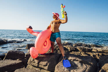 Man standing while holding flamingo ring and squirt gun against sea - MEUF02087