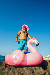 Man wearing hat standing on flamingo ring against clear sky - MEUF02090