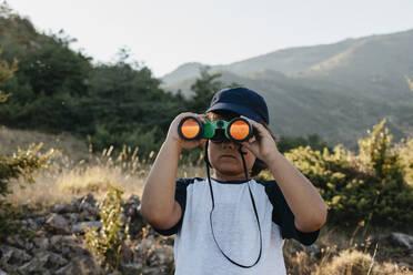 Boy using binocular while standing on mountain - VABF03480