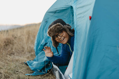 Smiling boy waving hand while sitting in tent - VABF03483