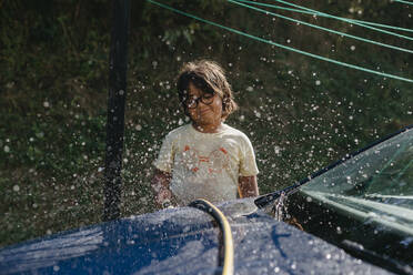 Boy standing and cleaning car with water - VABF03489