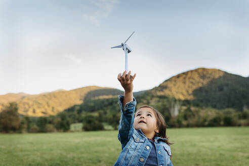 Cute girl playing with wind turbine toy while standing at backyard - VABF03510