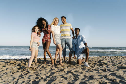 Young friends standing on sand against water during sunny day - RDGF00155