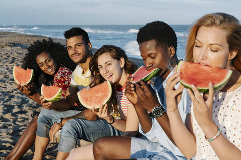 Friends eating slice of watermelon while sitting on beach during sunny day - RDGF00167