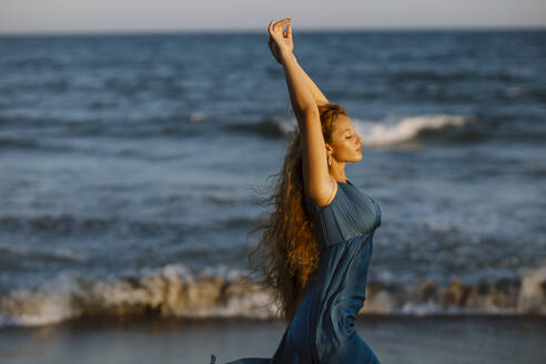 Beautiful woman with hand raised dancing while standing against sea - GMLF00618