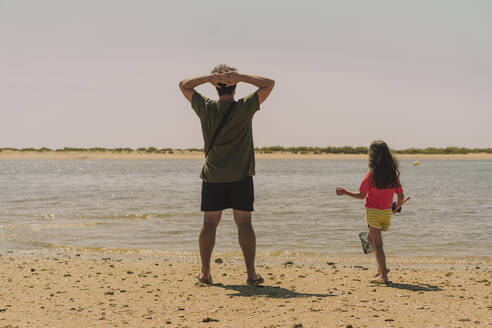 Father with daughter standing at beach against clear sky during sunny day - ERRF04422