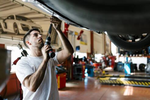 Young mechanic repairing car with work tool in auto repair shop - EGAF00781