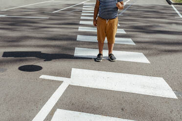Boy holding balloon while standing at crosswalk in city - VABF03513