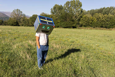 Boy with smiling cardboard box on face standing in meadow - VABF03522