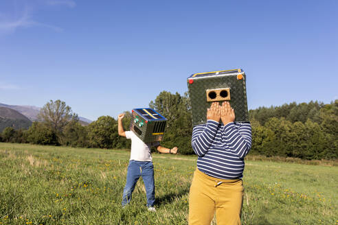 Boys playing with robot cardboard box while standing in meadow - VABF03525