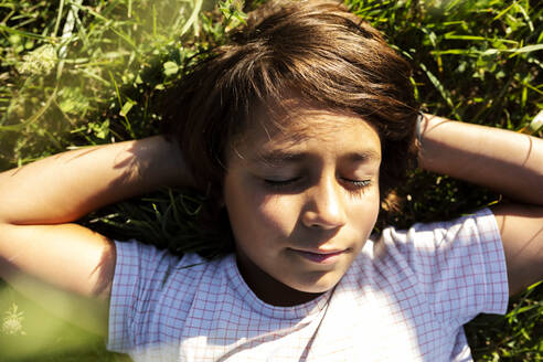 Boy with hands behind head sleeping on grass in meadow - VABF03528