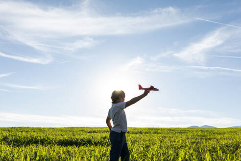 Carefree boy playing with airplane toy against clear sky - VABF03537