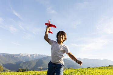 Smiling boy holding airplane toy while standing against clear sky - VABF03540