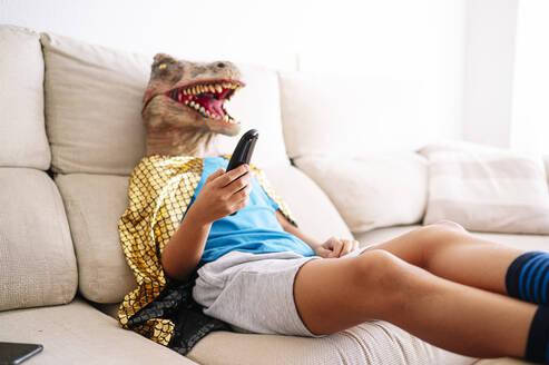 Boy wearing dinosaur mask watching TV while relaxing on sofa at home - JCMF01448