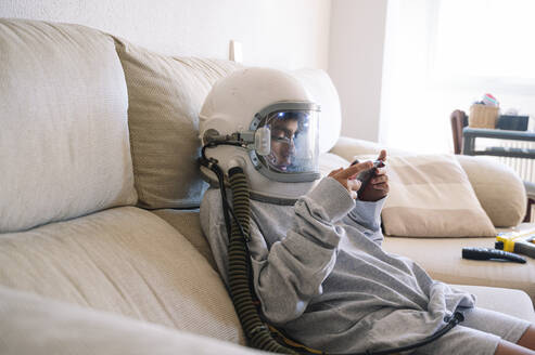 Boy wearing space helmet playing handheld video game while relaxing on sofa at home - JCMF01457