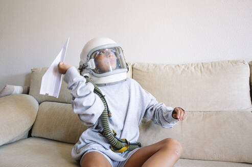 Boy wearing space helmet flying paper airplane while sitting on sofa at home - JCMF01460