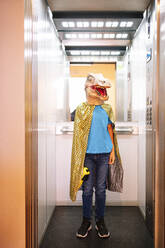Boy wearing dinosaur mask and cape standing in elevator - JCMF01469
