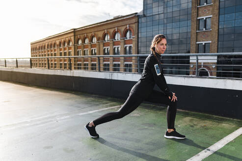 Female athlete stretching legs on rooftop against buildings in city - JMPF00406