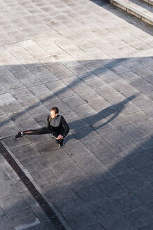 Female athlete stretching legs while crouching on rooftop - JMPF00421