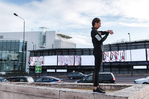 Female athlete checking time while standing on retaining wall against sky in city - JMPF00424